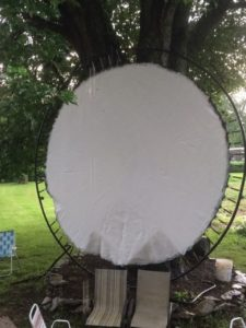 An upcycled repurposed trampoline being used as a projector screen.
